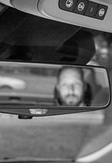 мужчина в зеркале заднего вида